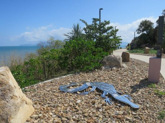 Image 5. A crocodile suns itself on rocks. In the background is Magnetic Island.